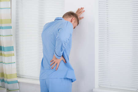 back ache: Man Suffering From Back Ache Standing Against Wall