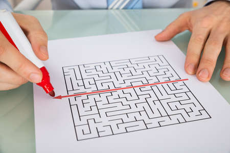 shortcut: Close-up Of A Person Hand Drawing Straight Red Line Over Maze With Red Marker