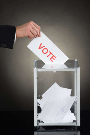 into: Close-up Of A Businessperson Hand Putting Vote Into Ballot Box Stock Photo