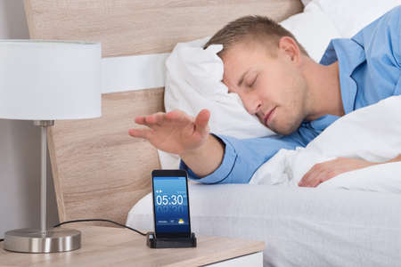 snooze: Man Lying On Bed Snoozing Alarm On Mobile Phone Screen