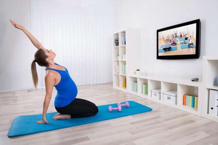 Young Pregnant Woman Exercising In Front Of Television At Home photo