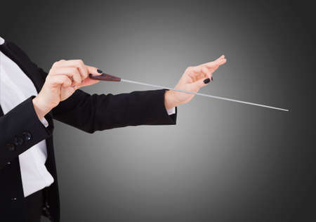 choral: Cropped image of female music conductors hands holding baton against gray background Stock Photo