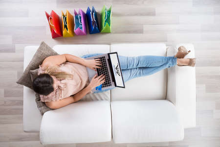 Young Woman Sitting On Sofa With Laptop Shopping Online Stock Photo