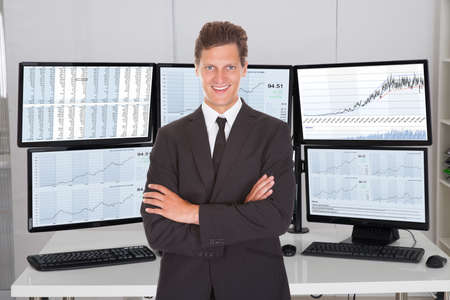 financial market: Portrait of stock market broker standing arms crossed against multiple screens in office
