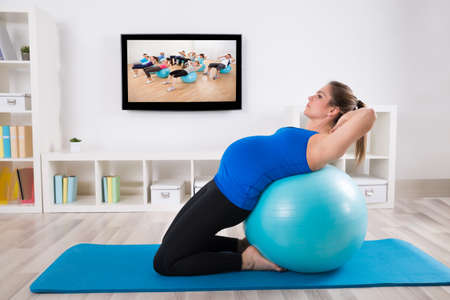 Pregnant Female Doing Workout On Fitness Ball In Front Of Television photo