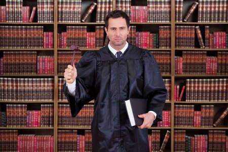 proceeding: Portrait of serious judge holding gavel and book against shelves Stock Photo