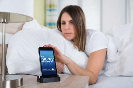 snoozing: Young Woman Lying On Bed Snoozing Alarm On Mobile Phone Stock Photo