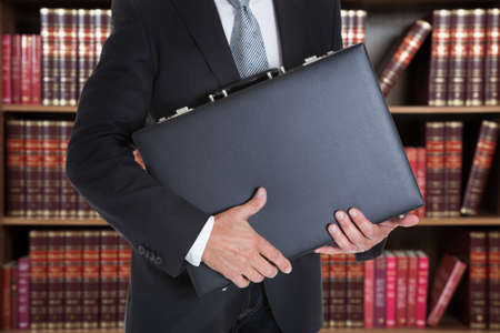 Midsection of businessman holding briefcase in office