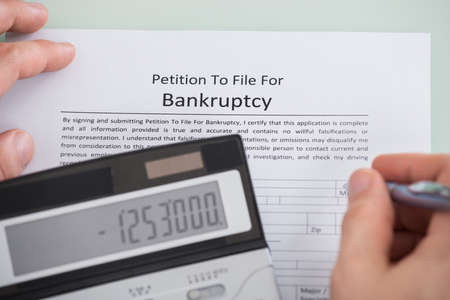 bekanntmachung: Close-up Of Person Hand And Calculator Over Bankruptcy Form