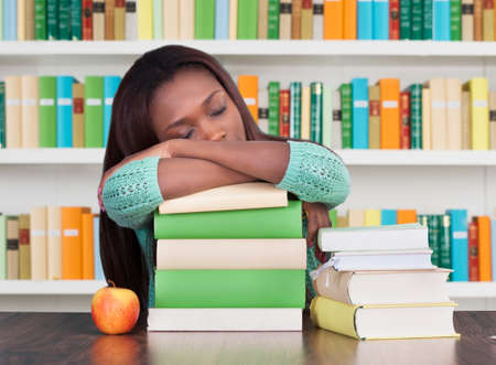 Tired university student sleeping on stacked books at desk in library Stock Photo