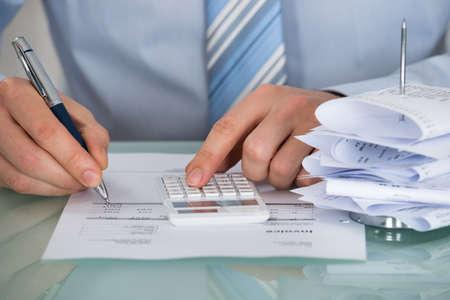 Close-up van zakenman berekenen Invoice In Office