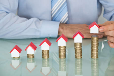 Close-up Of Businessman Arranging House Model On Stacked Coins At Desk Stock Photo