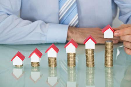 viviendas: Primer plano del hombre de negocios Organizar Casa modelo en monedas apiladas En El Escritorio