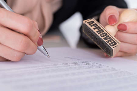 signing authority: Close-up Of Businessperson Hand With Pen And Wooden Stamp On Document Stock Photo