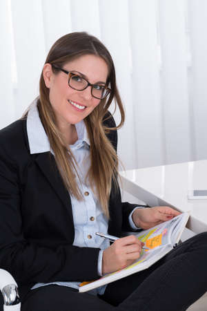 event planner: Young Happy Businesswoman Writing In Diary At Office