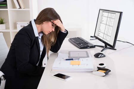 pc screen: Young Businesswoman Suffering From Headache At Workplace