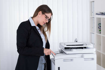 copy machine: Young Businesswoman Using Copy Machine At The Office