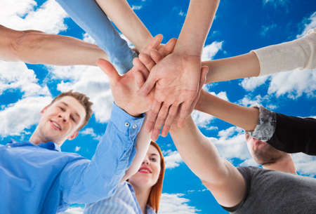 directly below: Directly below portrait of friends stacking hands against sky Stock Photo
