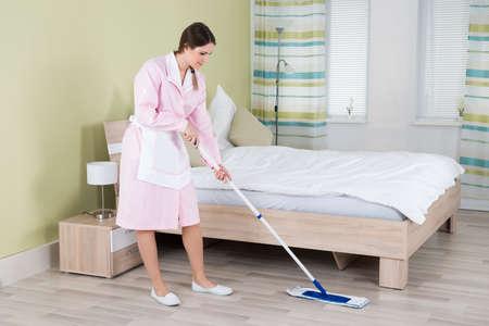 ama de llaves: Mujer joven ama de casa limpieza del piso con la fregona en la habitaci�n Foto de archivo
