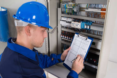 manual test equipment: Young Male Technician Holding Clipboard While Examining Fusebox Stock Photo