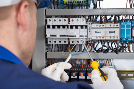 manual test equipment: Male Electrician Working On Fusebox With Screwdriver Stock Photo
