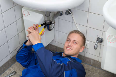 repairing: Young Male Plumber Repairing Sink In Kitchen Stock Photo