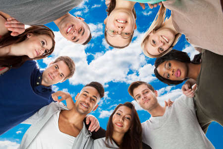 directly below: Directly below portrait of happy multiethnic college students forming huddle against sky
