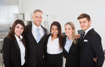 arms around: Portrait of multiethnic professionals standing arms around each other in office Stock Photo
