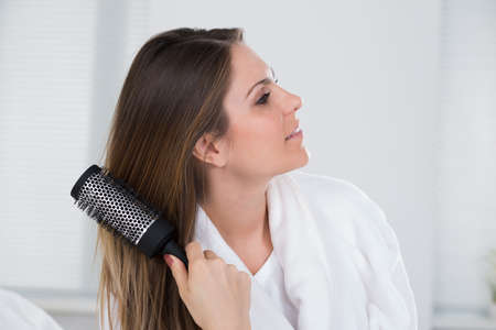 combing hair: Close-up Of A Woman Combing Her Hair