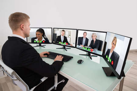 conferencing: Young Businessman Video Conferencing On Desk With Multiple Computers Stock Photo