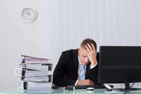 persona triste: Joven Hombre de negocios que duerme en el escritorio en la oficina Foto de archivo