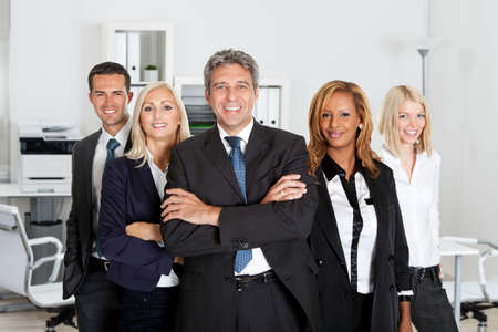 manager team: Portrait of confident business team standing together in office