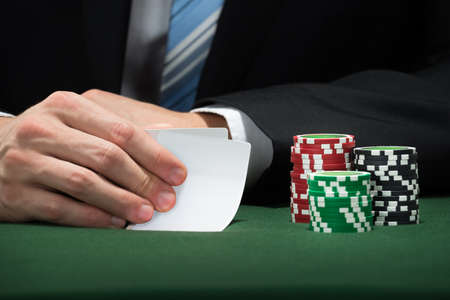 gamblers: Close-up Of Poker Player Hand With Cards And Chips Stock Photo