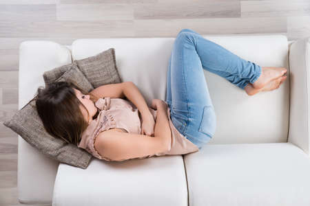 High Angle View Of Young Woman Napping On Sofa Stock Photo