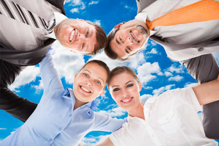directly below: Directly below portrait of confident business team forming huddle against sky