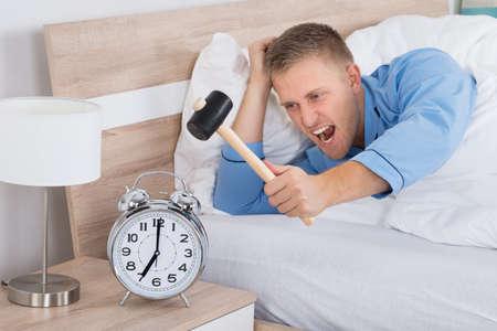 reloj despertador: El hombre joven Smashing Reloj despertador con el martillo en cama