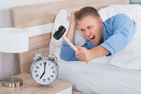 Young Man Smashing Alarm Clock With Hammer On Bed Фото со стока