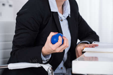 push: Close-up Of Businessperson Hand Squeezing Blue Stressball In Hand At Desk Stock Photo