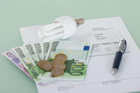 ahorro energetico: Primer plano de una bombilla de luz fluorescente con factura y moneda
