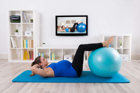 Young Pregnant Female Exercising In Front Of Television photo