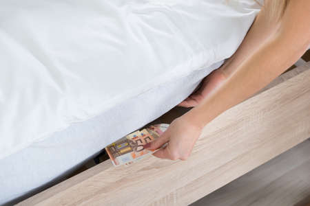 money risk: Close-up Of A Female Hand Hiding Banknotes Under Bed Stock Photo