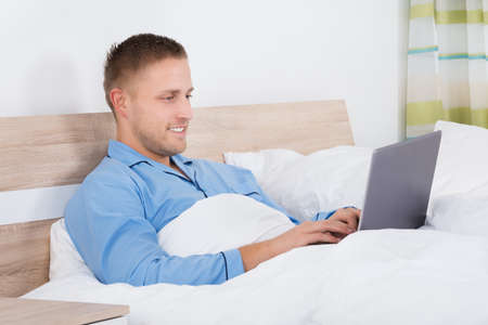 looking at computer: Happy Young Man Using Laptop On Bed In His Bedroom