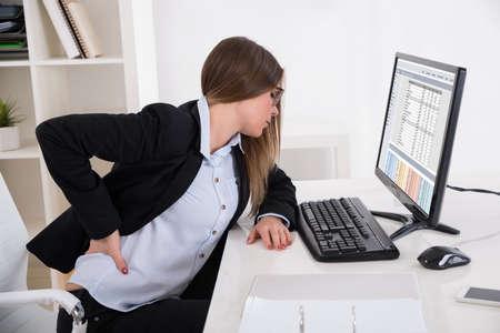 Giovane Imprenditrice Con Backpain seduto sulla sedia a posto di lavoro