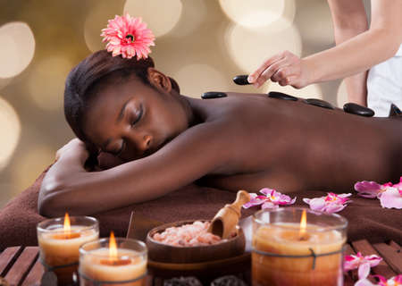 Relaxed young woman receiving hot stone therapy in beauty salon