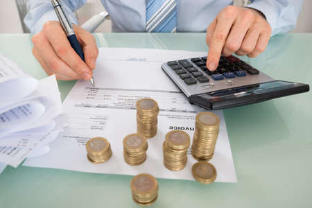 INVOICE: Close-up Of Businessman Calculating Invoice With Coins At Desk