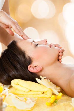 masaje facial: Vista lateral de la mujer joven que recibe masaje de la cabeza del masajeador en el spa de belleza