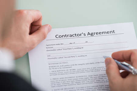 agreement: Close-up Of Person Hand Over Contractors Agreement Form Stock Photo