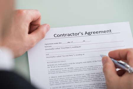 Primer plano mano de la persona sobre la forma Acuerdo de contratista Foto de archivo