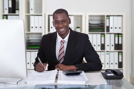 Portrait of smiling male accountant writing on documents at desk in office