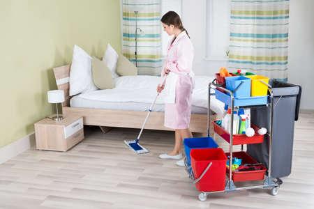 housekeeper: Mujer joven ama de casa Mopping piso en la habitaci�n